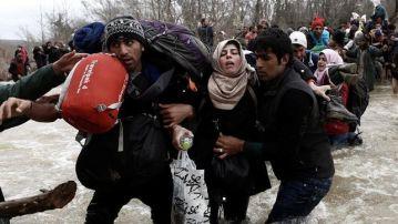 Un grupo de refugiados ayudándose a cruzar un río para pasar la frontera entre Grecia y Macedonia