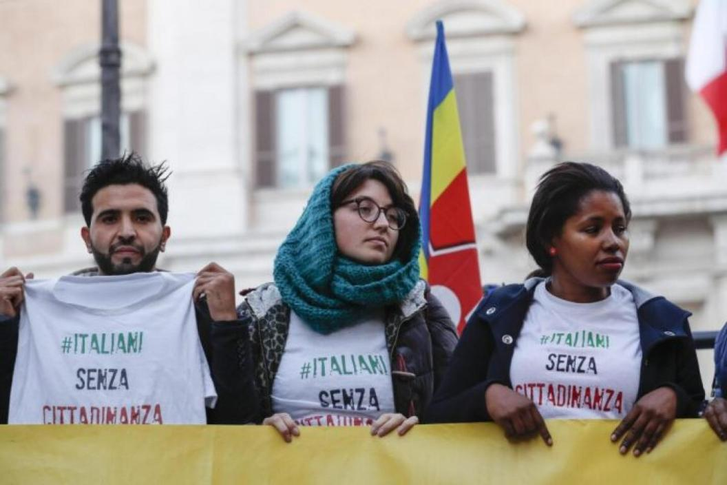 dos mujeres y un varón inmigrantes protestan en Italia