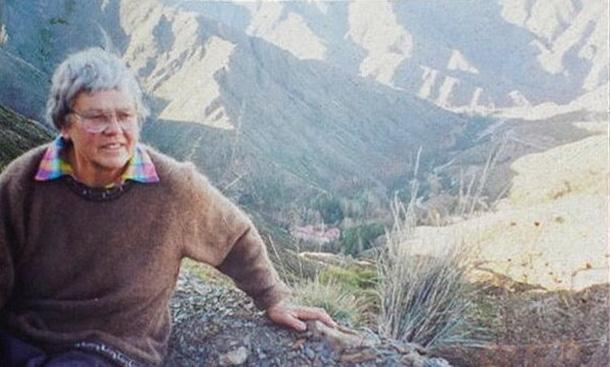 Odile sentada en una roca, al fondo montañas y un valle