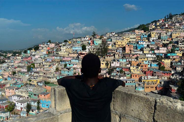 un muchacho afroamericano observa apoyado en un balcón de bloques de cemento sin terminar. Al fondo la ladera de un cerro con cientos de casitas humildes de muchos colores. El cielo está un poco nuboso y casi no se aprecia vegetación.