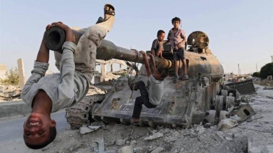 cuatro muchachos juegan alegres en las calles. al fondo se aprecia un paisaje desolado, fruto de la guerra. los muchachos están sobre los restos de un tanque de guerra, uno de ellos está muy sonriente y se columpia cabeza abajo desde el cañón