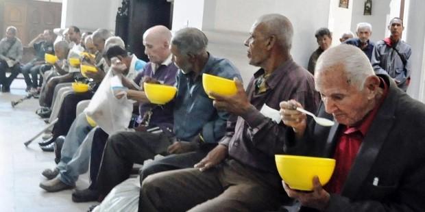 Unos quince varones ancianos caraqueños toman sopa servida en bowls y cucharas plásticas. Están sentados en los bancos del templo. Al fondo varias personas esperan su turno, se ve también un confesionario antiguo de madera. Todos tienen rostros serios, de preocupación.