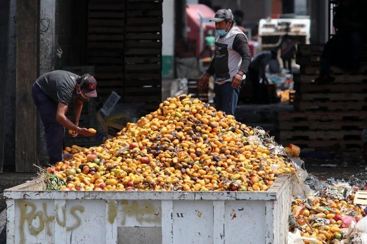 dos personas llegan a escoger productos que todavía sirvan para su consumo en contenedores de restos de frutas y verduras