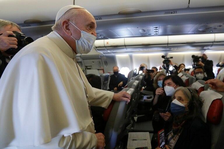 Francisco de pie en el pasillo del avión. Usa tapabocas y apoya su mano en un asiento. Los periodistas escuchan y apuntan sus cámaras desde sus asientos.