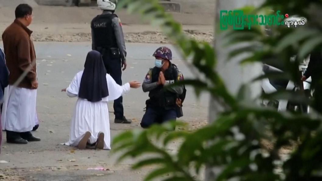 una monja con los brazos abiertos está arrodillada frente a dos policías. uno de ellos se arrodilla y suplica juntando las palmas, el otro permanece de pie