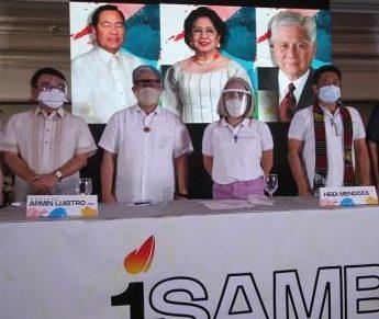 tres hombres y una mujer de mediana edad están de pie tras la mesa de una conferencia de prensa. el hombre y la mujer al centro llevan crucifijos. los cuatro usan tapabocas y llevan camisas blancas de manga corta. detrás hay una pantalla con tres rostros de políticos posando.