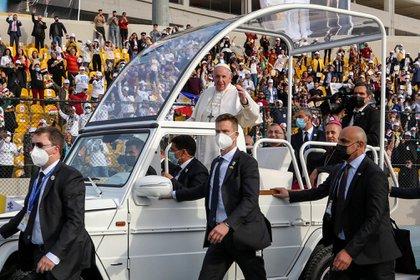 el Papa saluda desde el papamóvil, custodiado por varios hombres a pie que usan traje negro. Al fondo la gente saluda de pie desde la tribuna. Muchos usan tapabocas y muestran banderas de Irak. Son hombres y mujeres en vestimenta tipo occidental