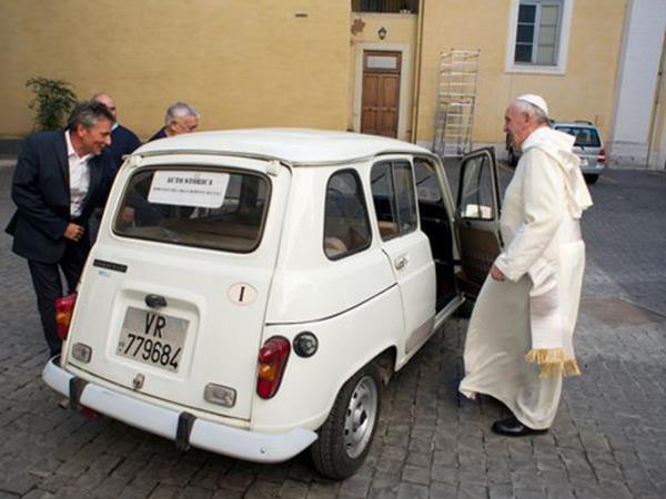 Francisco pronto a subir de acompañante en la Renault 4 que le fuera regalada. Parece contento. La antigua camioneta luce bien, y está estacionada en un patio vaticano, varios hombres observan el auto.