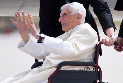 Benedicto saluda sonriente con las dos manos extendidas desde la silla de ruedas. Vestidura y solideo blancos, lleva reloj de pulsera de gran esfera blanca