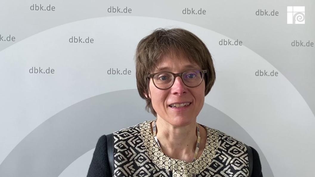 foto de torso de la dra. Gilles, que sonríe durante una conferencia de prensa. Al fondo parte del logo de la Conferencia Episcopal y web de la misma: dbk.de