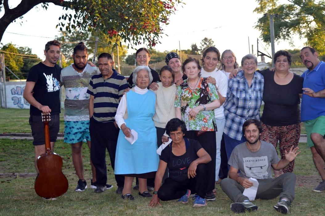 15 personas posan alegres cerca de un ceibo en flor, en foto tipo familiar
