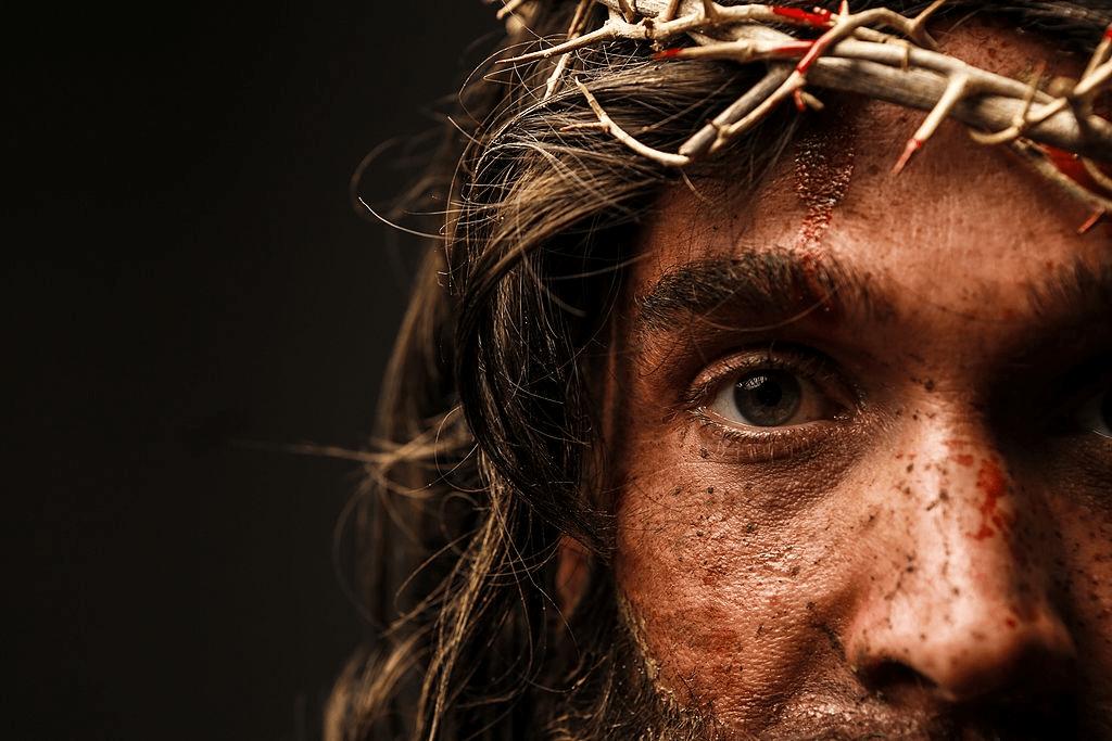 imagen parcial del rostro de un actor representando a Jesús. Lleva corona de espinas, con lastimaduras sangrantes. Mirada clara hacia el frente. fondo neutro, como de una pared.