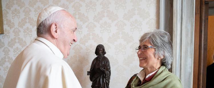 María visita a Francisco, están frente a frente y sonríen ambos. ella es más baja, cabello gris y usa lentes