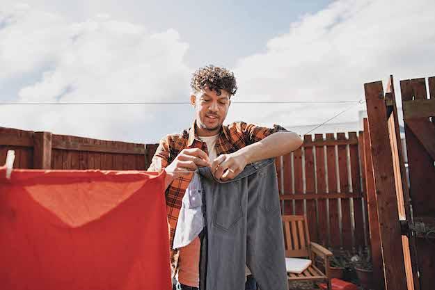 hombre joven de vestimenta informal, que usa una alianza, tendiendo la ropa en el patio. parece contento.