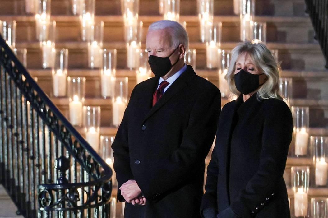 Biden y su esposa parados al pie de una escalera en la Casa Blanca. Visten ropa oscura formal y llevan tapabocas. Sobre los escalones están las velas encendidas, perfectamente espaciadas, cada una en su contenedor de vidrio.