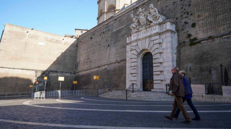 vista de la entrada del museo vaticano. la explanada está desierta, salvo por una pareja que pasa caminando. se ve el pórtico de piedra con sus esculturas arriba y la gran puerta completamente cerrada