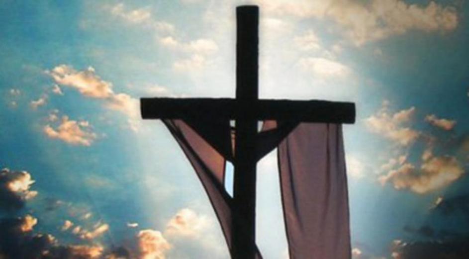 vista de la cruz vacía, un lienzo cuelga doblado sobre ella. atrás un cielo con nubes y brillo de sol