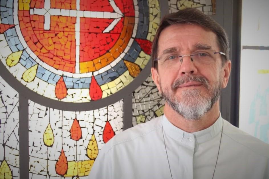 retrato del obispo Lisboa, que sonrie levemente. viste camisa blanca cuello mao, barba corta y canosa. es de mediana edad y cabello castaño. lleva lentes con cristal montado al aire. al fondo un vitral con motivo pentecostés