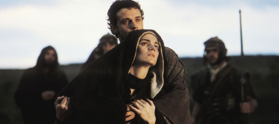 fotograma en primer plano de María y Juan al pie de la cruz. juan sostiene a maría, que se toma de su brazo. los dos miran impactados hacia la cruz, aunque ésta no se ve. al fondo se ven tres personas, dos son guardias armados. los rostros de los discípulos están sutilmente iluminados.