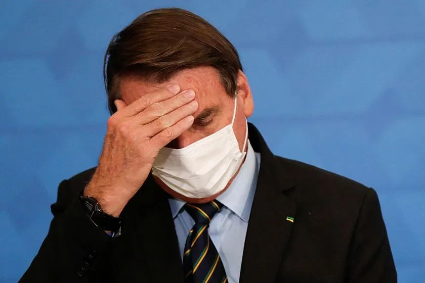el presidente brasilero baja la cabeza y se toca la frente con la mano abierta. de ojos cerrados, usa tapabocas. lleva traje y corbata, en la solapa un pin verdeamarelho
