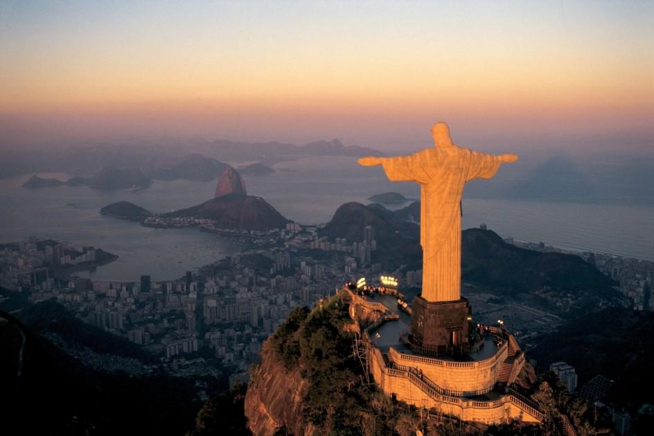foto aerea del cristo redentor del corcovado, en rio de janeiro. la estatua esta iluminada desde atras por el sol de la tardecita, al fondo se ven la ciudad y el mar