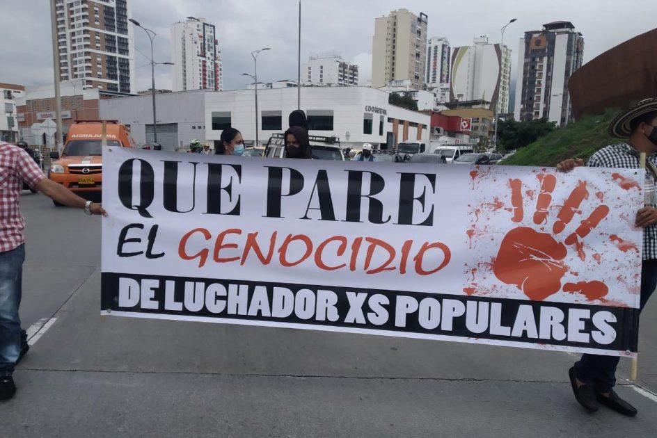 marcha por las calles de bucaramanga, el dia de comienzo del tribunal. dos personas portan un cartel que corta el transito. se lee: que pare el genocidio de luchadorxs populares y se ve una huella grande de una mano impresa en rojo salpicado