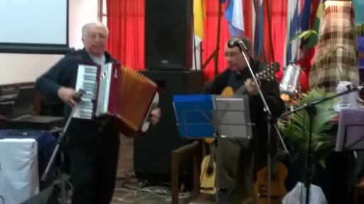 heriberto sentado frente a la partitura, tocando guitarra. a su lado julio tocando acordeón, con el fuelle desplegado.