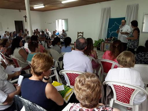 heriberto habla a la audiencia, que esta sentada en sillas plasticas. detras, el mapa de la diocesis