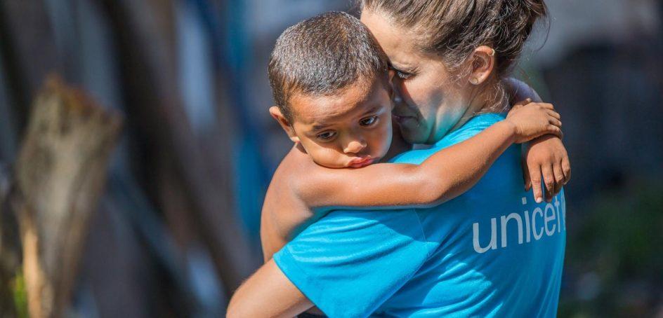 una trabajadora social con camiseta de unicef sostiene a upa a un niño de unos tres años que la abraza. el niño parece triste, con su mirada perdida hacia el suelo. la voluntaria tiene los ojos bien cerrados y toca con su frente la cabeza del niño. el fondo esta muy desenfocado, parece un paisaje del tropico.