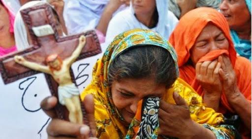 dos cristianas indias lloran durante una manifestación. son mayores y secan sus lágrimas con sus vestiduras. una de ellas levanta un crucifijo hacia la cámara. detrás, unas cinco personas observan.