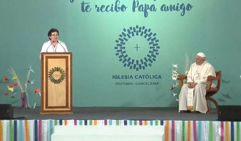 nellyu esta hablando desde un pulpito, en un escenario. el papa sentado a unos cuatro metros, la mira atentamente, las manos tomadas sobre su regazo. al fondo del escenario se lee: te recibo papa amigo.