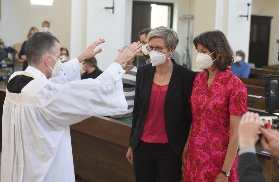 un sacerdote aleman bendice a una pareja de dos mujeres de edad mediana. ellas estan tomadas de la mano, frente al cura que les impone las manos. todos llevan tapabocas.