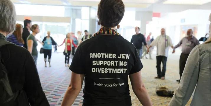 vista parcial de una ronda de unas 24 personas tomadas de las manos. en primer plano una mujer de espaldas con una camiseta que dice, en ingles: otra judia apoyando la desinversion, voz judia para la paz.