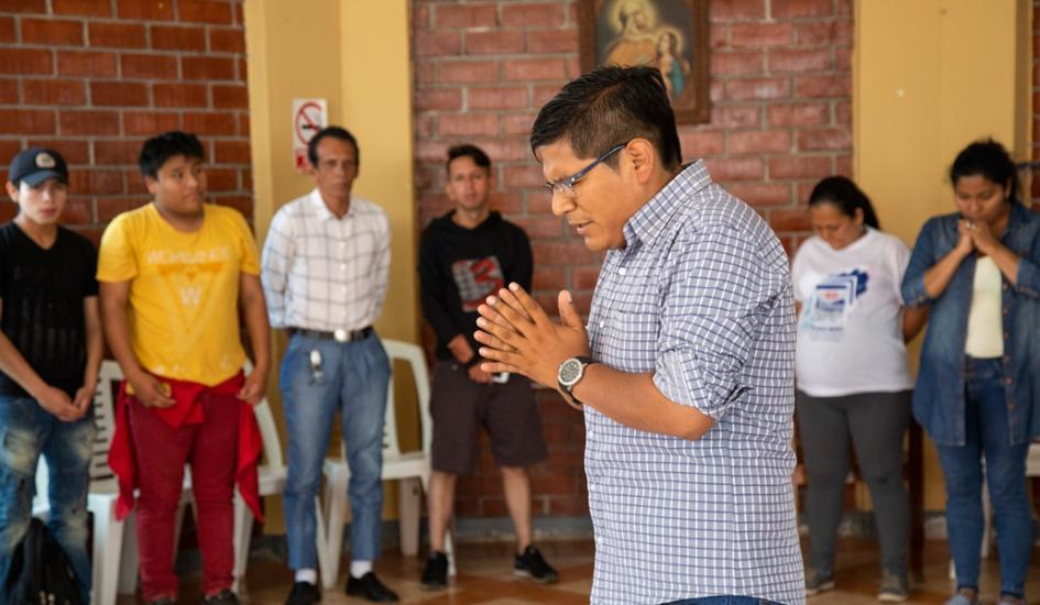 un grupo de catequesis de adultos: al centro el catequista, esta de pie, con las manos juntas como rezando. esta de ojos cerrados y levemente inclinado hacia adelante. participan cuatro hombres y dos mujeres a su alrededor