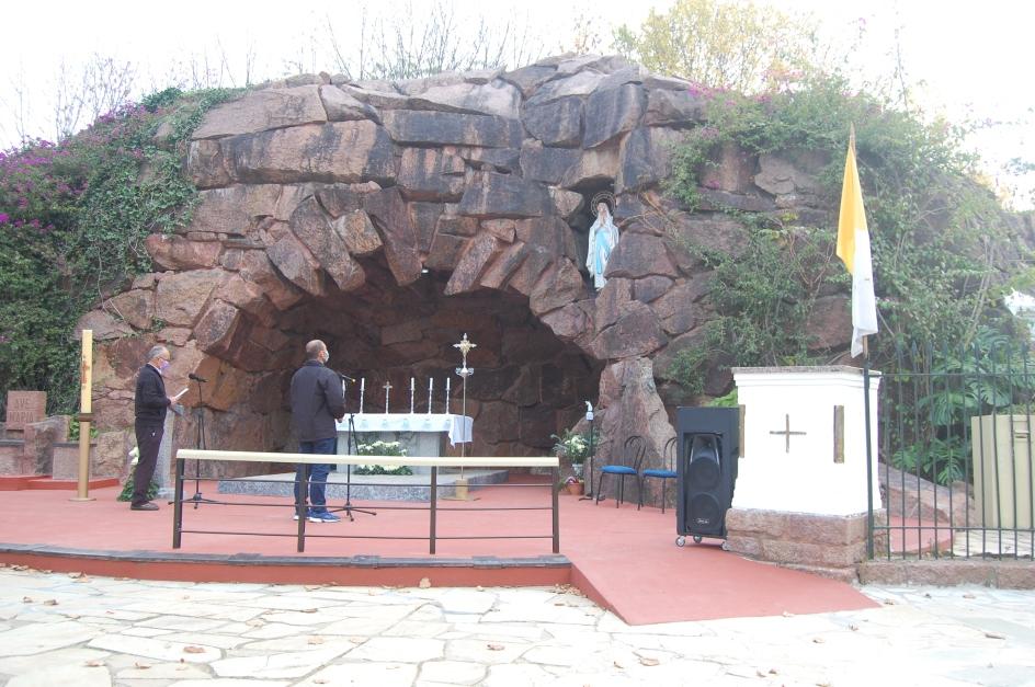 dos personas rezan el rosario frente a la gruta de lourdes de montevideo