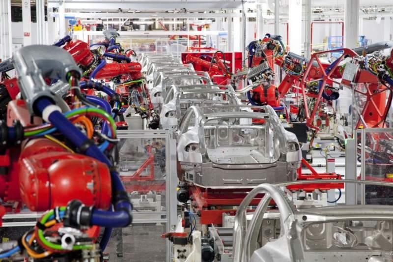 linea de produccion en una gigafactoria de autos tesla. se aprecian unos diez esqueletos del model 3 que estan siendo ensamblados por coloridos robots. es una nave enorme y muy iluminada y ordenada. no se ve ningun humano.