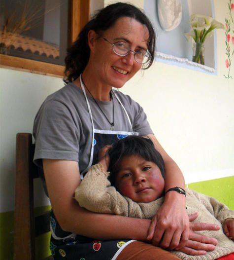 retrato de nadia, que sonrie sentada en una silla, sus brazos abrazan a un niño peruano de unos cuatro años, que se deja caer sobre su regazo.