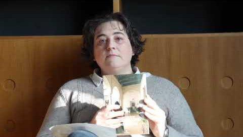 la autora fotografiada con su libro. ella esta recostada y muestra la tapa hacia la camara. usa un buzo gris y lleva cabello corto despeinado. mira al frente con gesto serio, un rayo de sol se proyecta en su torso.