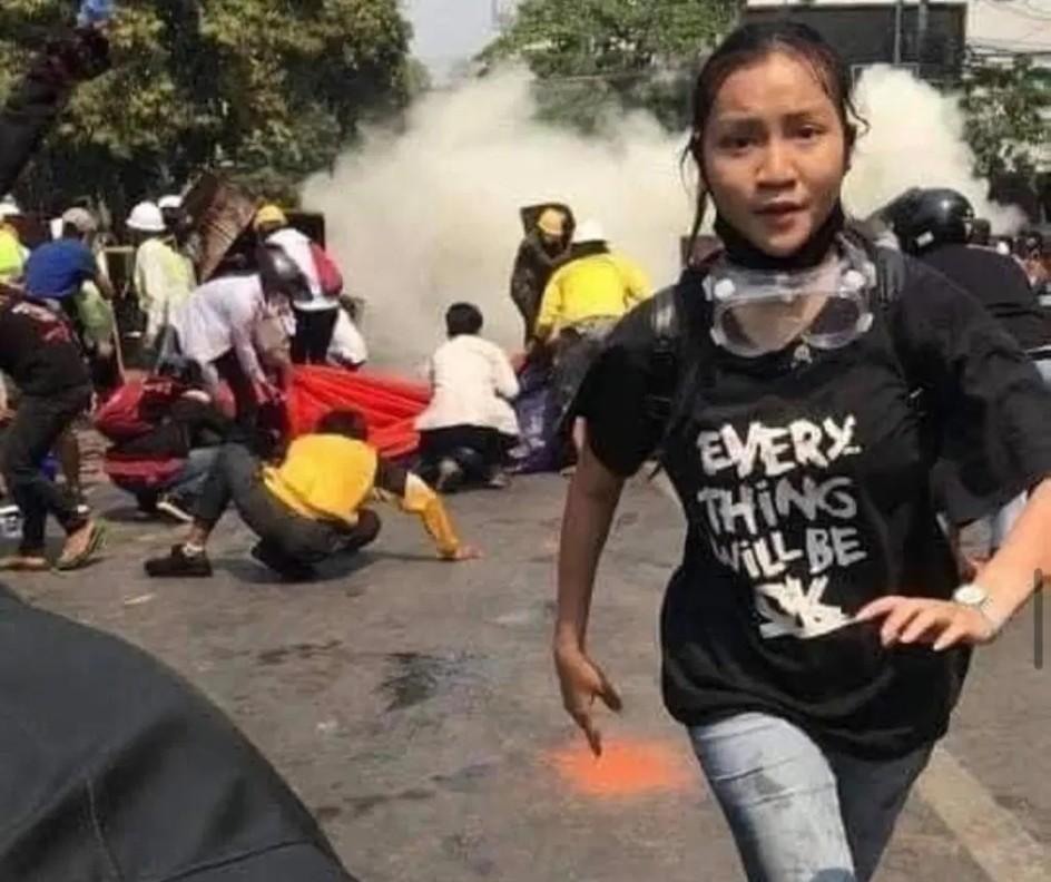 primer plano de una muchacha birmana que sale corriendo de la explosion de gases lacrimogenos durante una manifestacion en la calle. la mascarilla y unas antiparras caidas mas abajo del menton. mira a la camara con rostro acorde al momento. su camiseta negra dice, en letras blancas: todo estara ok, en ingles. al fondo se ven personas que se agachan ante la nube de gas.