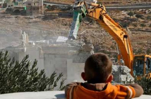 una maquina esta demoliendo una vivienda palestina. un niño, de espaldas, observa desde un balcon.