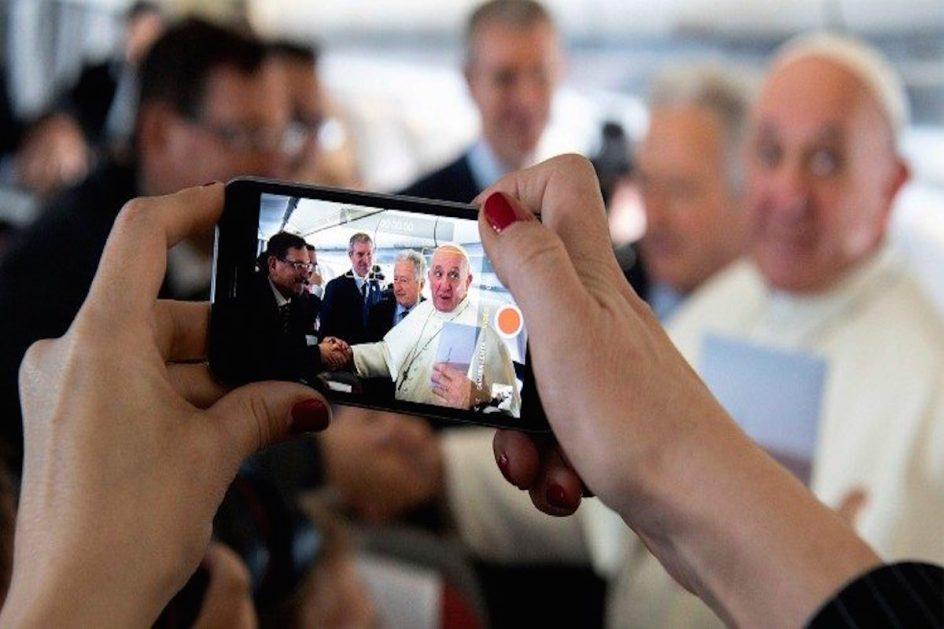 primer plano de dos manos sosteniendo un celular que esta fotografiando al papa francisco, que saluda a un señor con un apreton de manos.