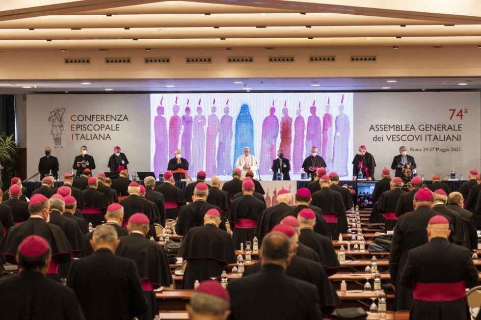 foto de la asamblea de obispos. al fondo una mesa larga con el papa al centro, cuatro obispos a su derecha y cuatro a su izquierda. detras una ilustracion acerca de pentecostes, con los doce y maria muy estilizados