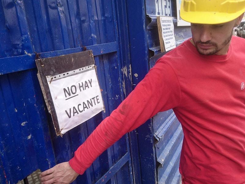 obrero de la construccion sale del predio de una obra con su casco amarillo puesto. es joven, de barba candado y lleva una camiseta roja de manga larga. el porton de chapa tiene un cartel que dice no hay vacante