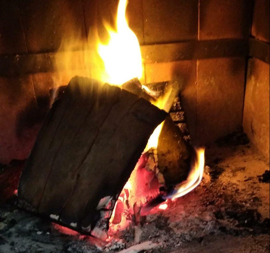 primer plano de un fuego encendido en una estufa a leña. son astillas grandes y arden muy bien. la llama es bien amarilla y alta. hay poco humo.