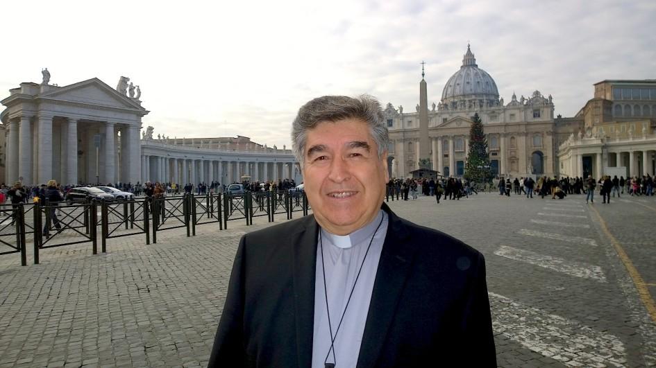 el obispo arizmendi sonrie en un retrato en plaza san pedro. lleva saco negro, camisa gris y usa clerigman. al fondo la gente forma fila frente a la basilica. se aprecia un arbol de navidad de unos 8 metros de altura.
