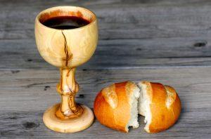 sobre una mesa de madera clara y veteada, se ven el pan y el vino. es un pan chico partido al medio, el vino esta servido en una copa de madera muy veteada, como de nogal u olivo.