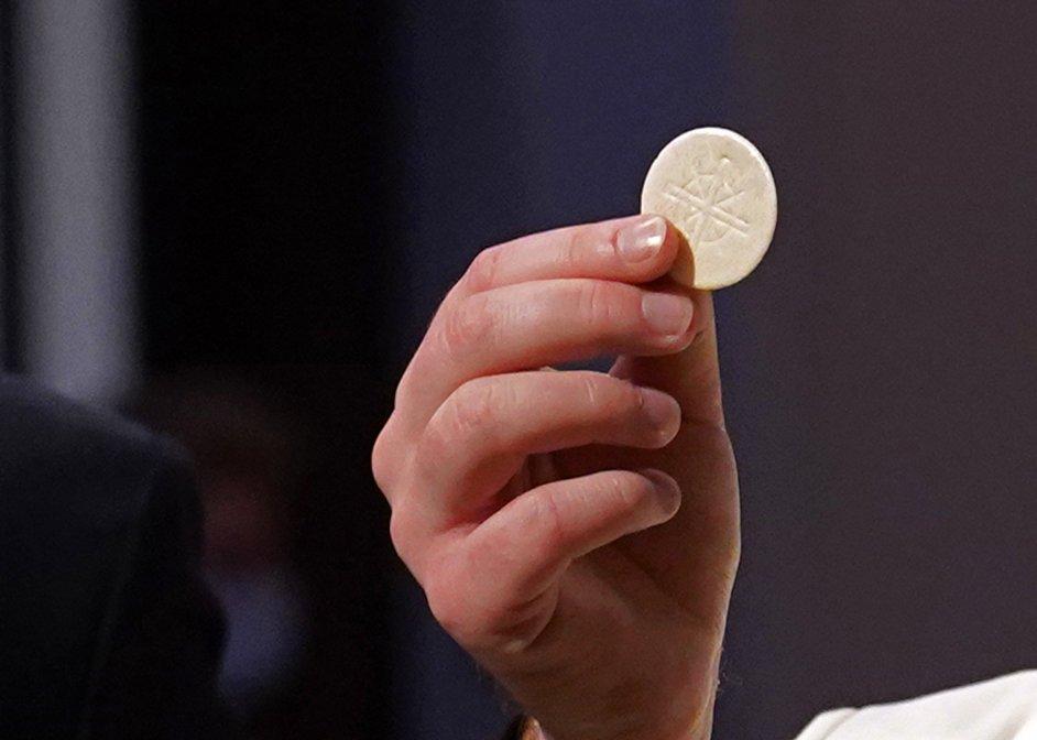 mano del sacerdote con la hostia, al ofrecer la comunion