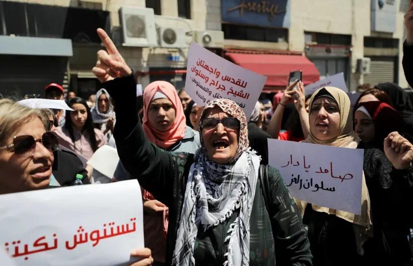 varias mujeres palestinas protestan en las calles de jerusalem. en primer plano una mujer mayor levanta su indice y parece gritar. mas atras mujeres jovenes sostienen carteles en arabe y en hebreo, algunas llevan la cabeza cubierta.