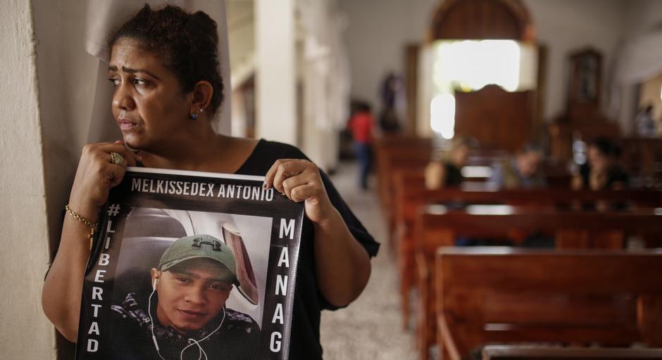en un templo, una madre sostiene la foto de su hijo preso mientras mira melancolica hacia afuera. en los marcos de la foto se lee melquisedex antonio, libertad, managua.