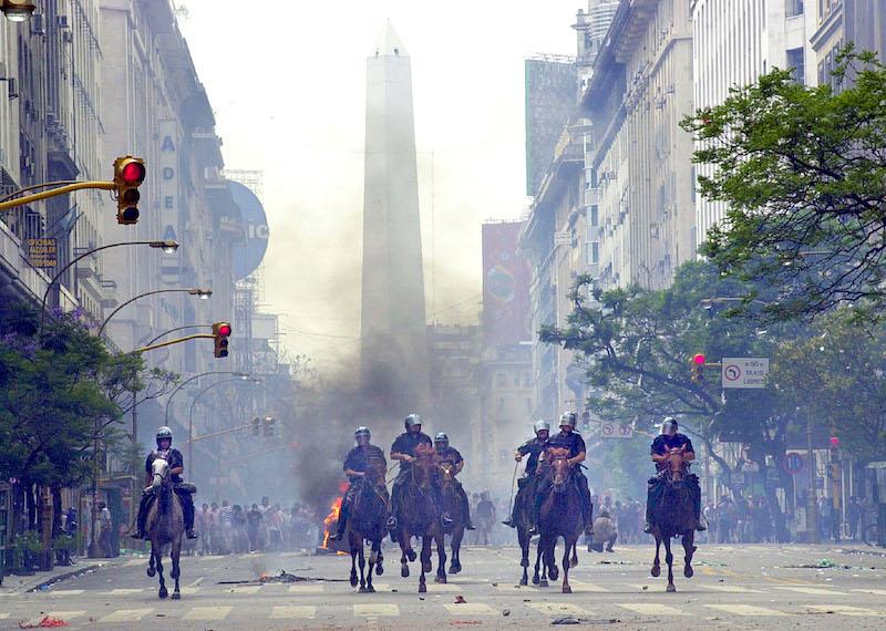 policias a caballo durante la represion en diciembre de 2001 por las calles de buenos aires. al fondo se ve el obelisco y los manifestantes, tras las llamas y el humo negro